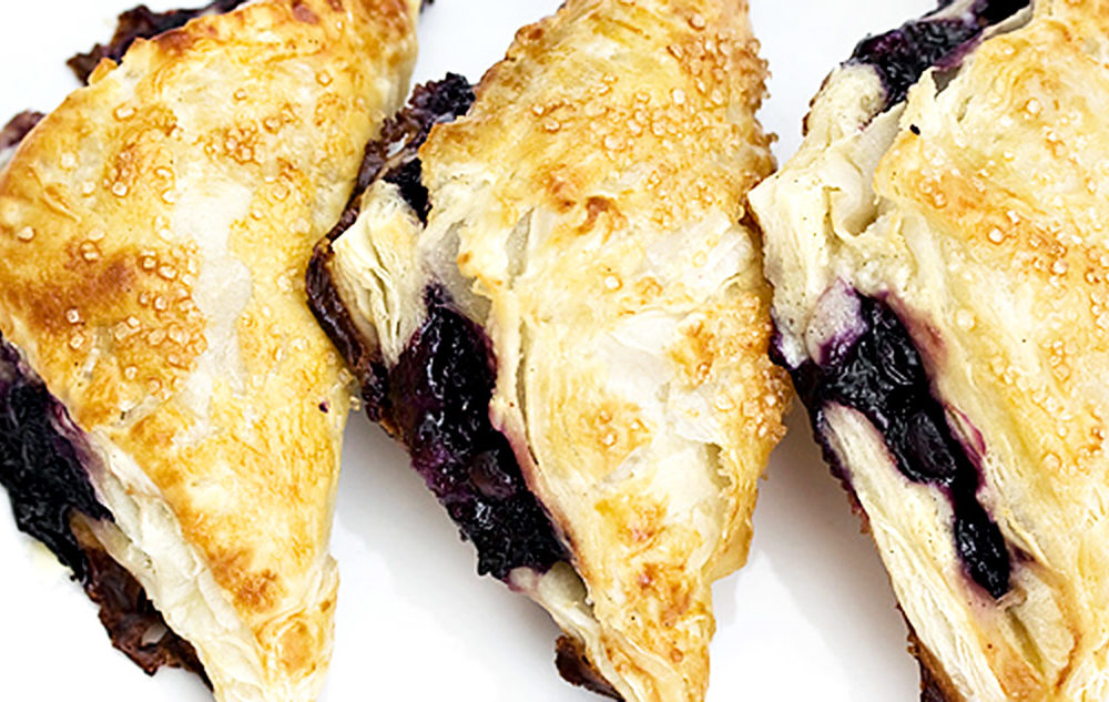 puff pastry blueberry turnovers on white background