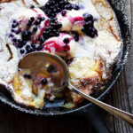 peach Dutch baby with blueberry sauce in cast iron skillet