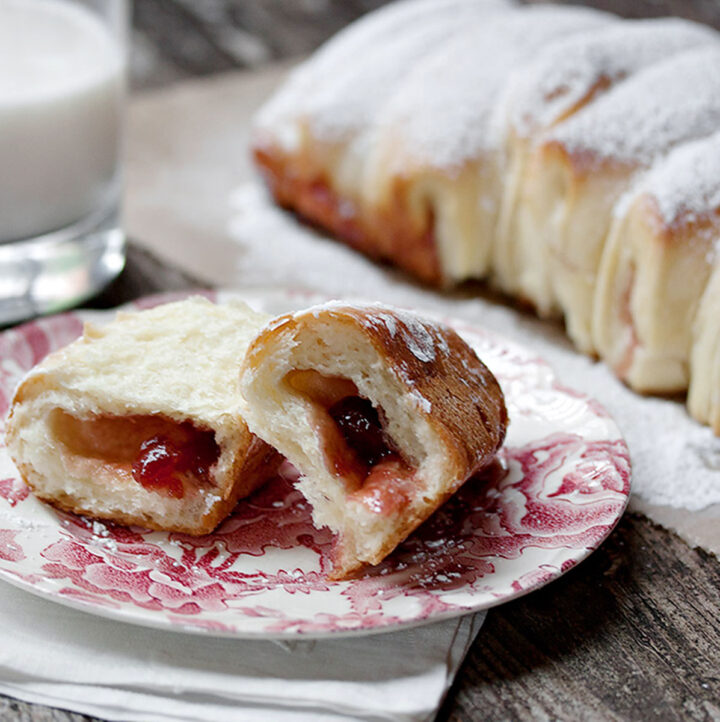 raspberry jam filled pull apart bread with a piece on a small plate