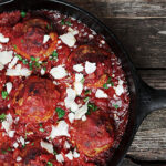 baked meatballs and tomato sauce in cast iron skillet