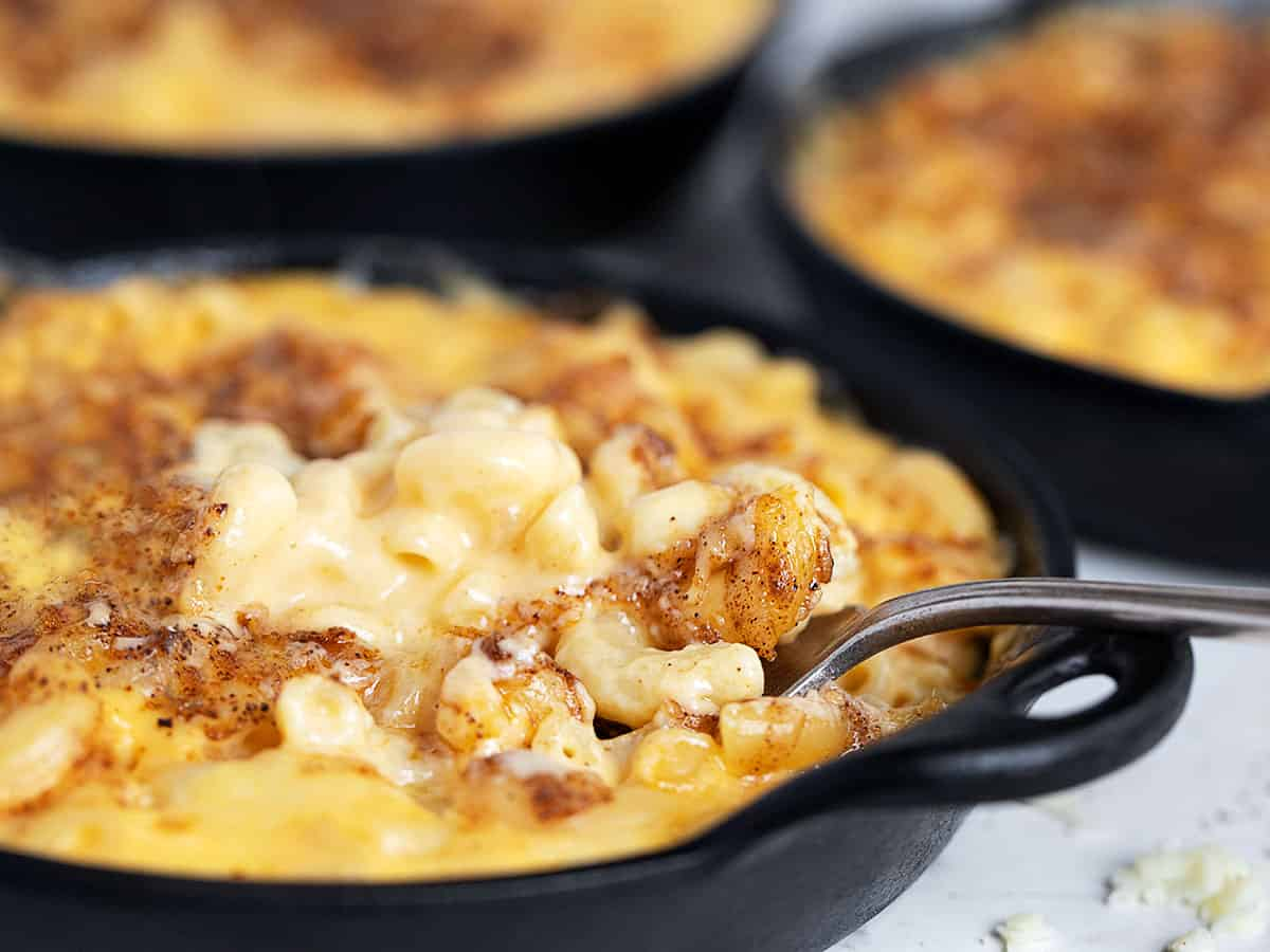 creamy mac and cheese in cast iron skillets with fork