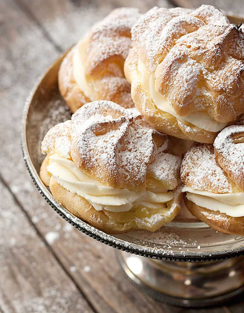 cannoli cream filled cream puffs on silver stand