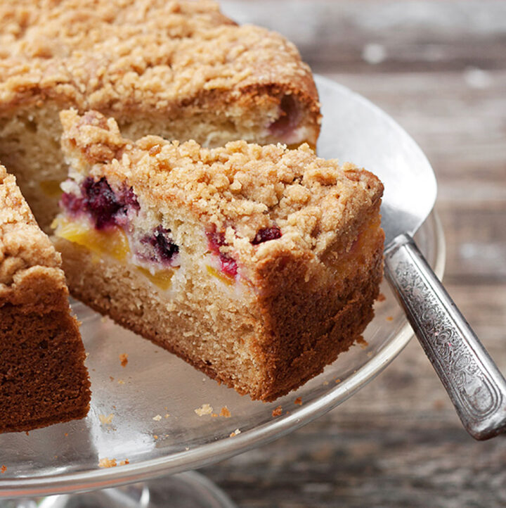 peach and berry streusel cake on cake stand sliced