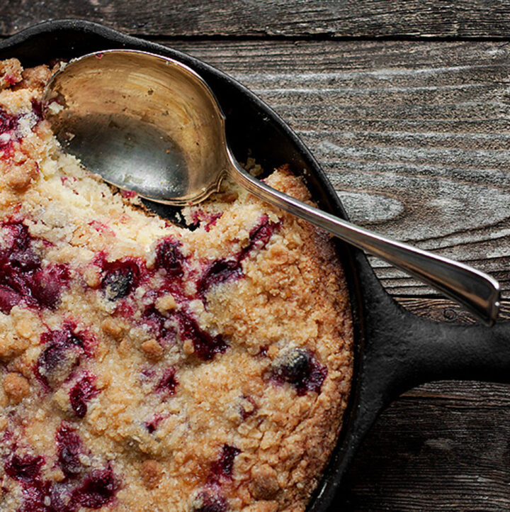 cranberry buckle cake in cast iron skillet with spoon