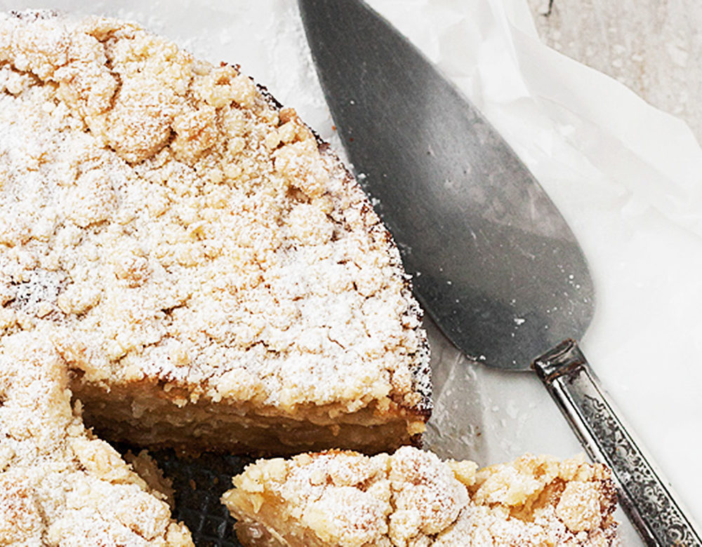 apple crumb cake on parchment with server