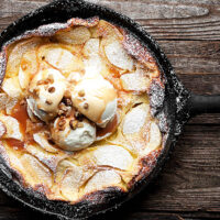 Dutch baby with apples and caramel sauce in cast iron skillet