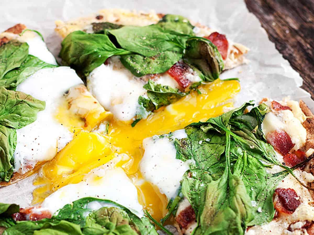 breakfast pita pizza sliced on parchment