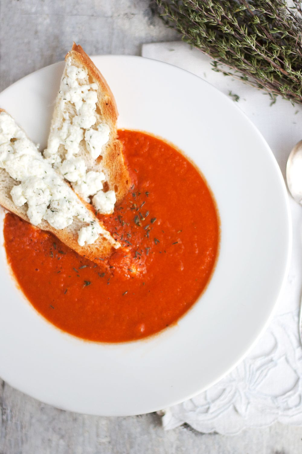 homemade tomato soup in white bowl with goat cheese toasts