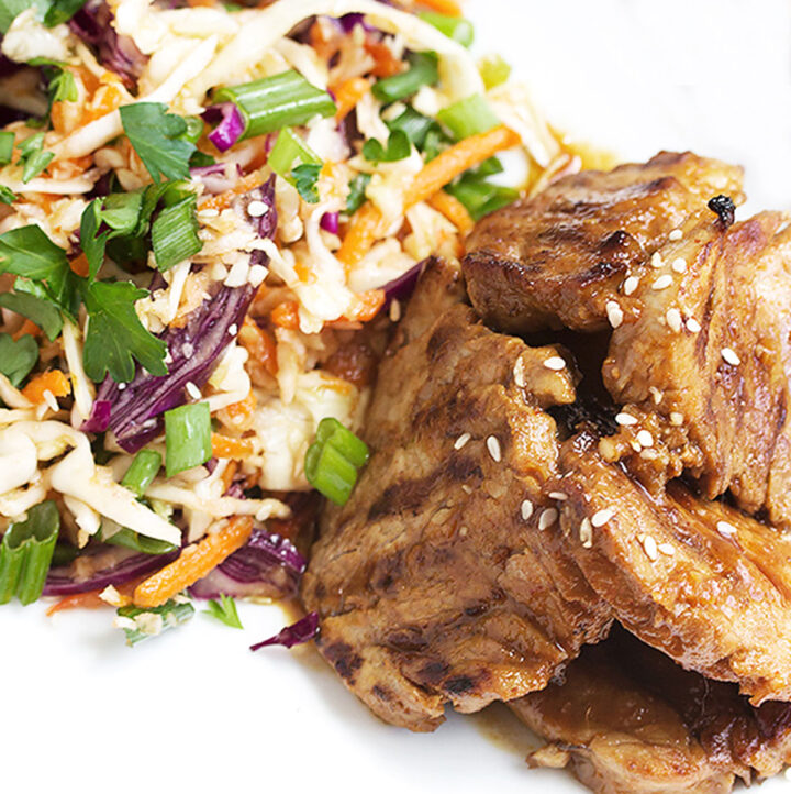 spicy Korean pork with Asian slaw on white plate