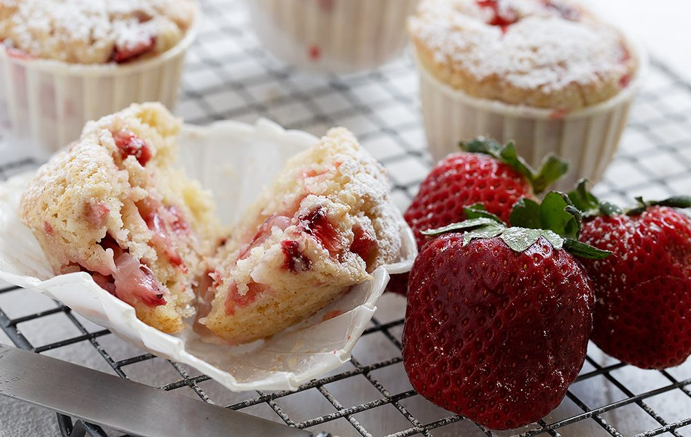 strawberry shortcake muffins on cooling rack with strawberries