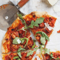chorizo and manchego cheese pizza sliced on parchment