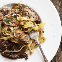pasta with mushrooms and mustard sauce in bowl with fork