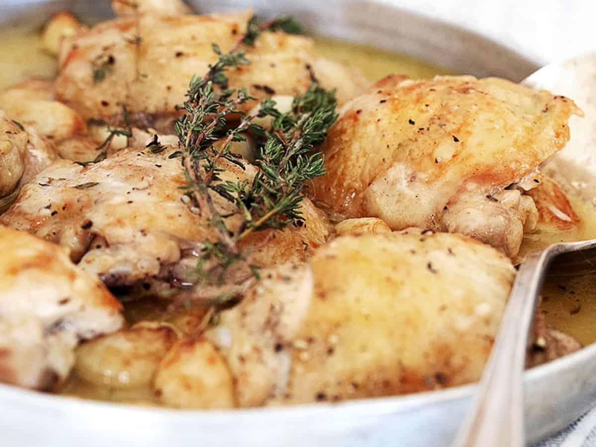 chicken with garlic gravy in serving dish with spoon