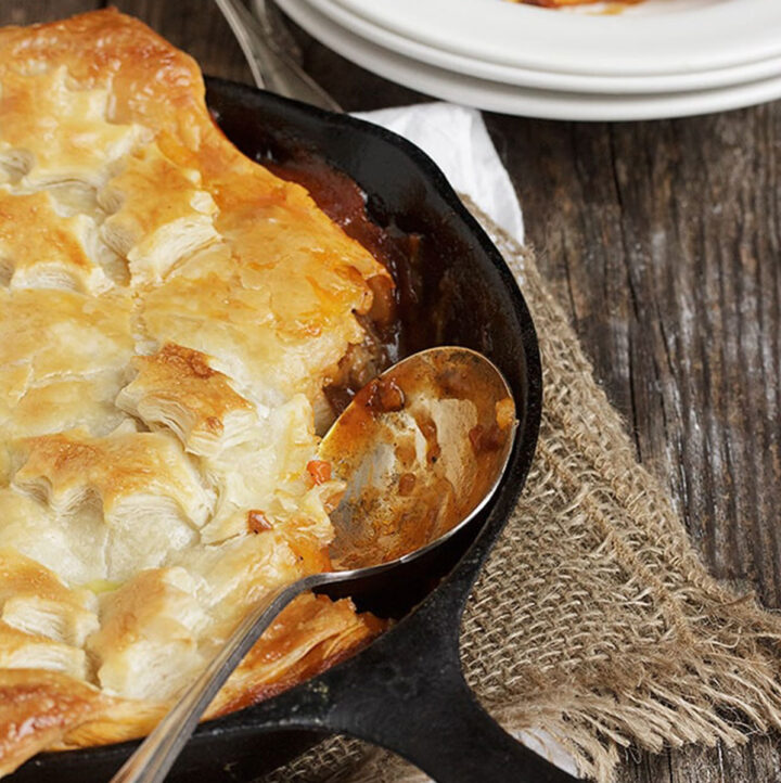 Beer-Braised beef and vegetable pie with puff pastry in skillet
