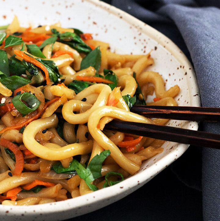 spicy udon noodles in bowl with chopsticks
