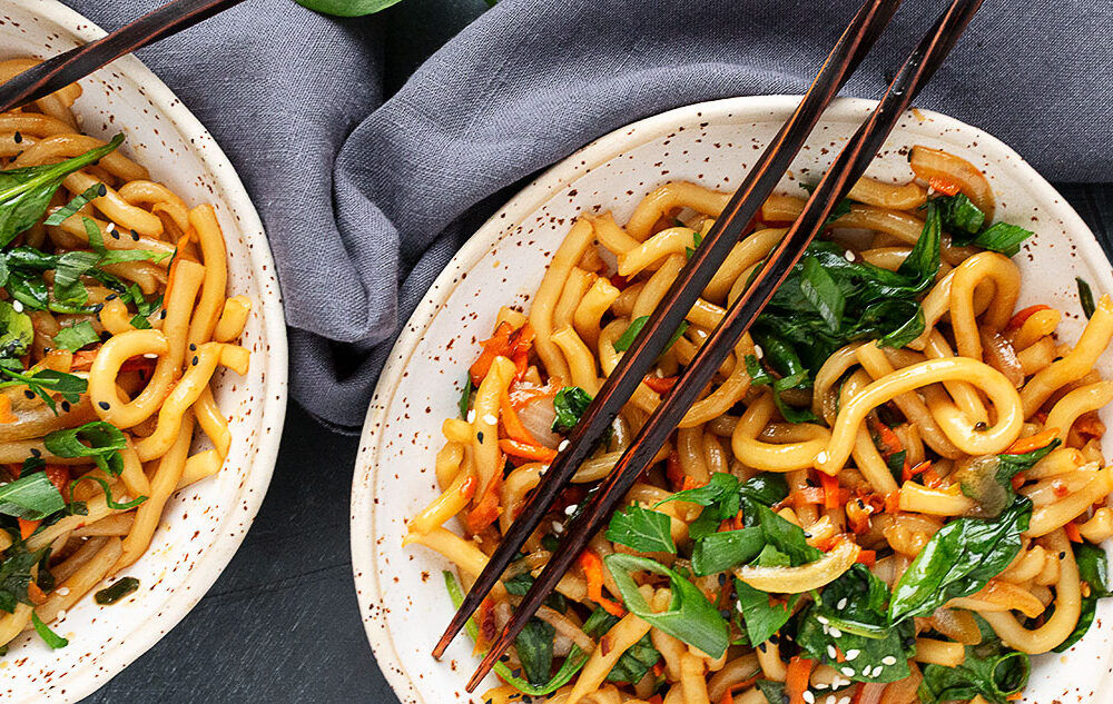 spicy udon stir fry in bowls from overhead