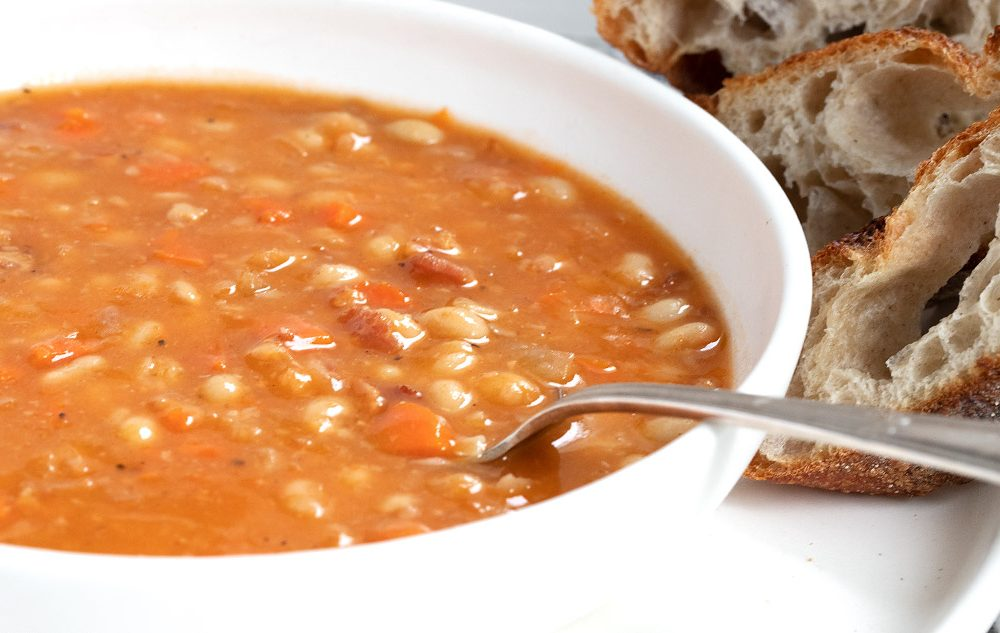 bean with bacon soup in white bowl