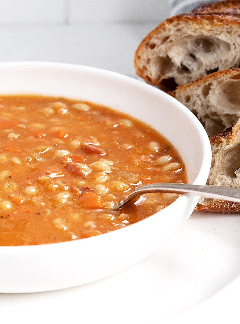 bean with bacon soup with bread slices in white bowl