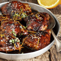 Asian sticky chicken in serving bowl with spoon