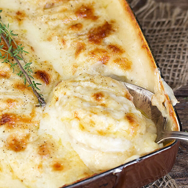 scalloped potatoes with bacon and cheese in casserole dish