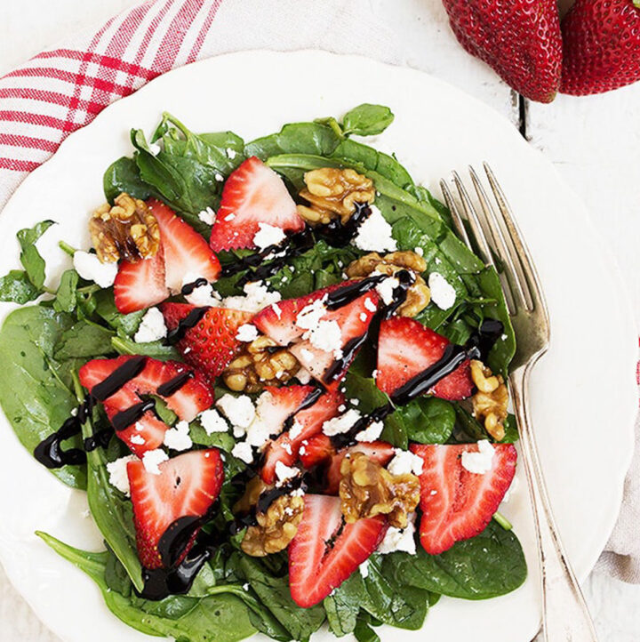 strawberry spinach salad on white plate