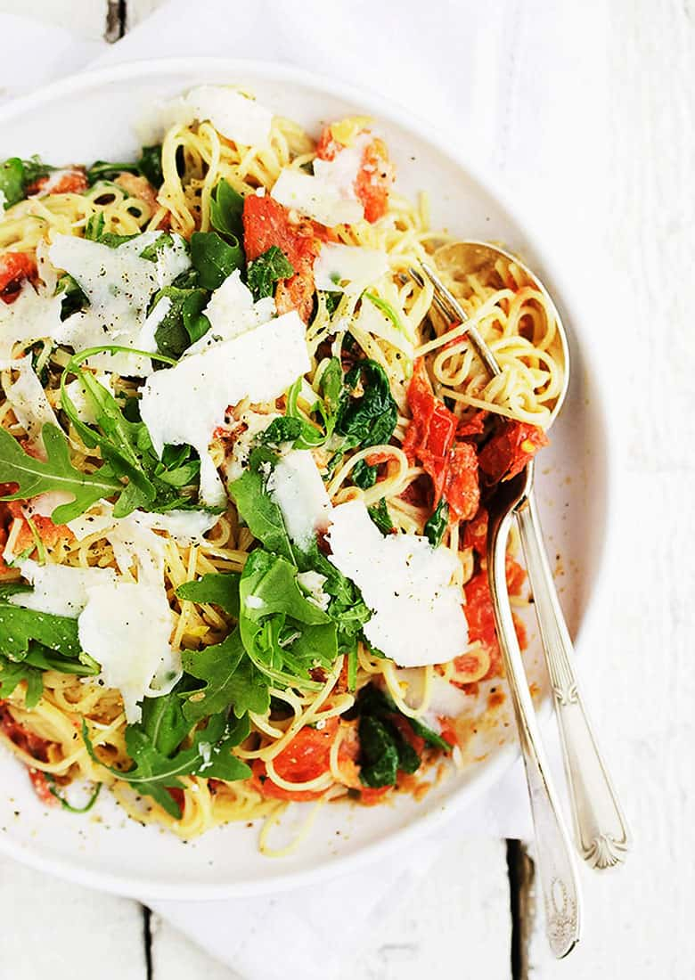 pasta with mascarpone and blistered tomatoes on white plate