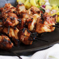 grilled chicken skewers on plate with pineapple salsa