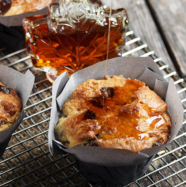 butter tart muffins on cooling rack with maple syrup bottle
