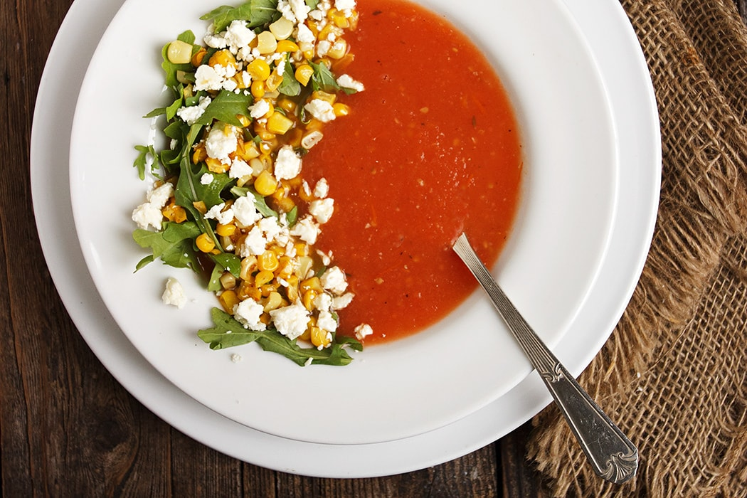tomato soup in white bowl, garnished with corn and feta