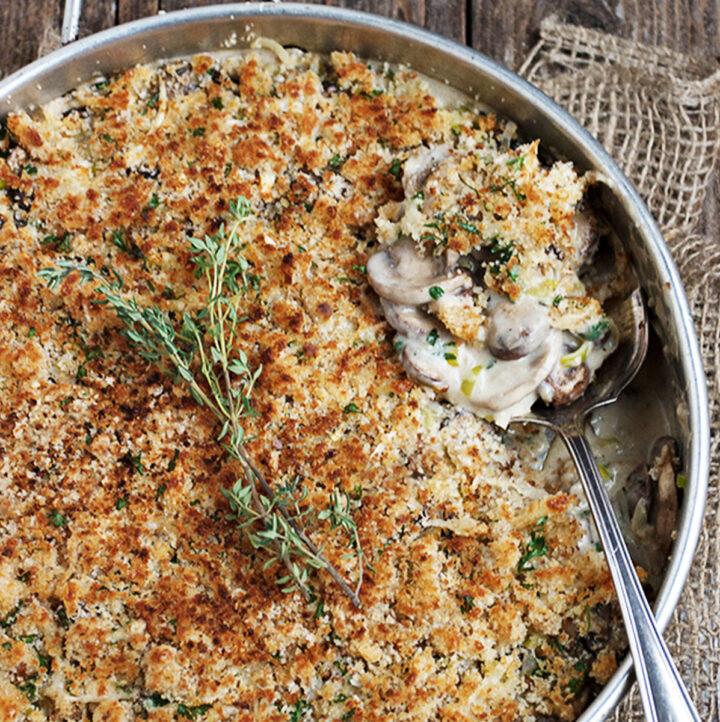 mushroom leek gruyere casserole in baking pan with spoon