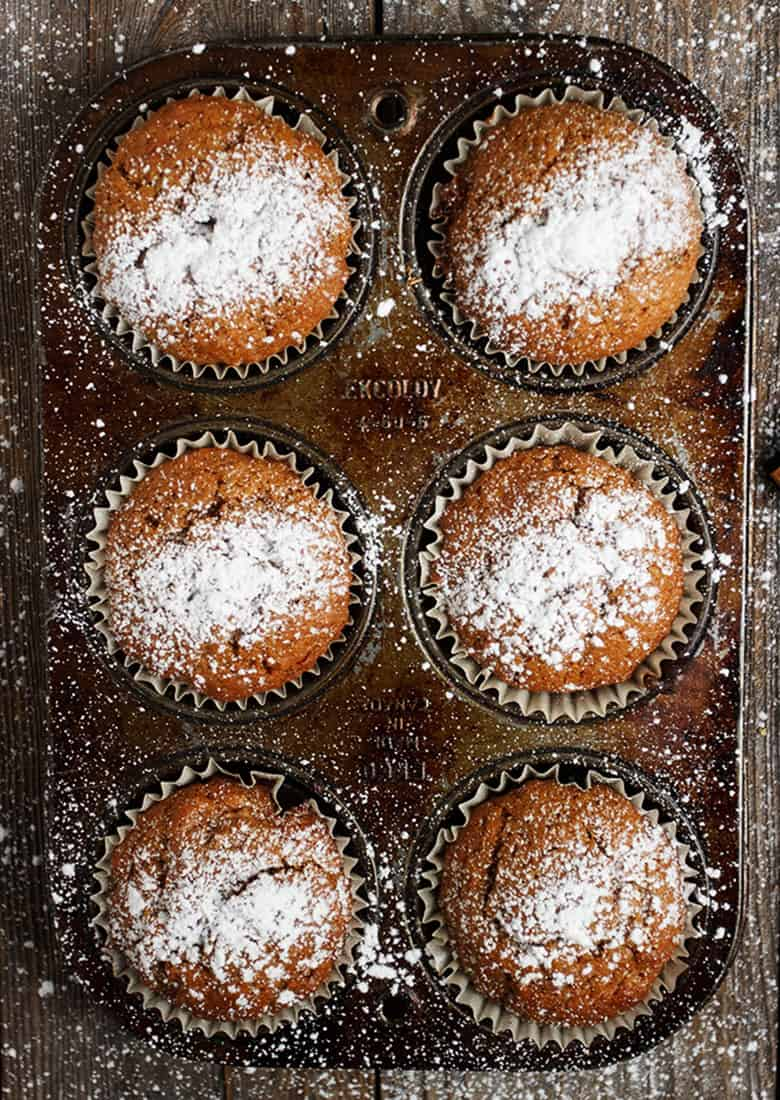 gingerbread muffins in muffin tin with powdered sugar on top