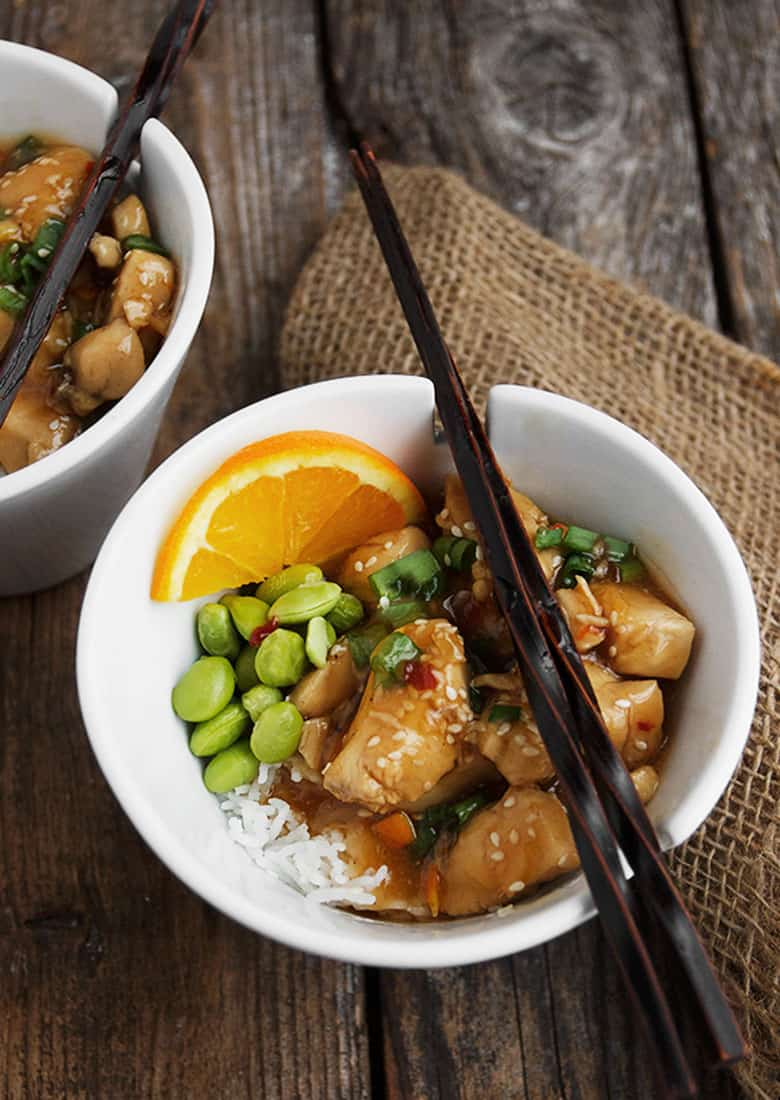 orange peel chicken in bowl with rice and edamame