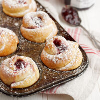 rose shaped buns in muffin tin with raspberry jam
