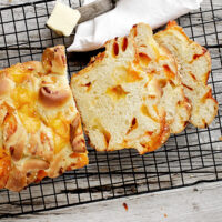 homemade chunky cheese bread sliced on cooling rack