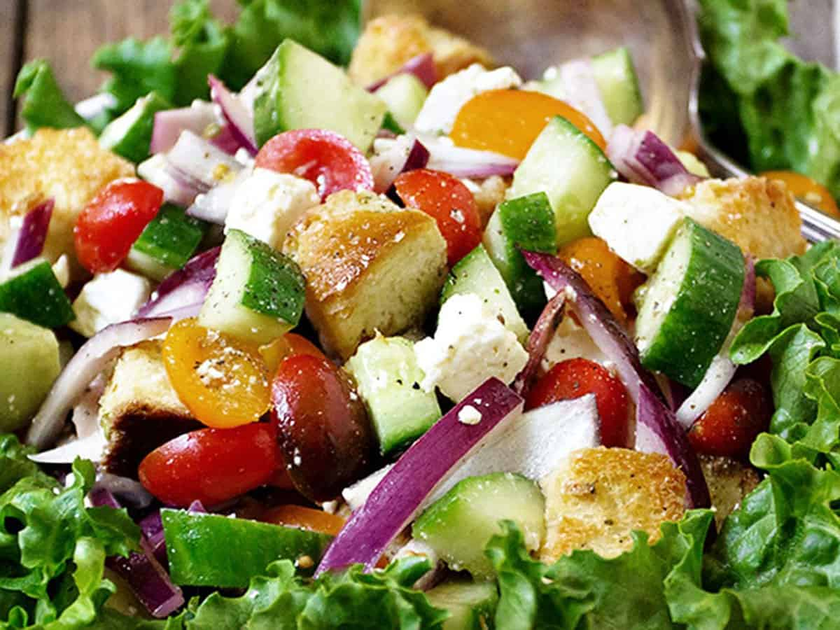 Greek panzanella salad in bowl with spoon