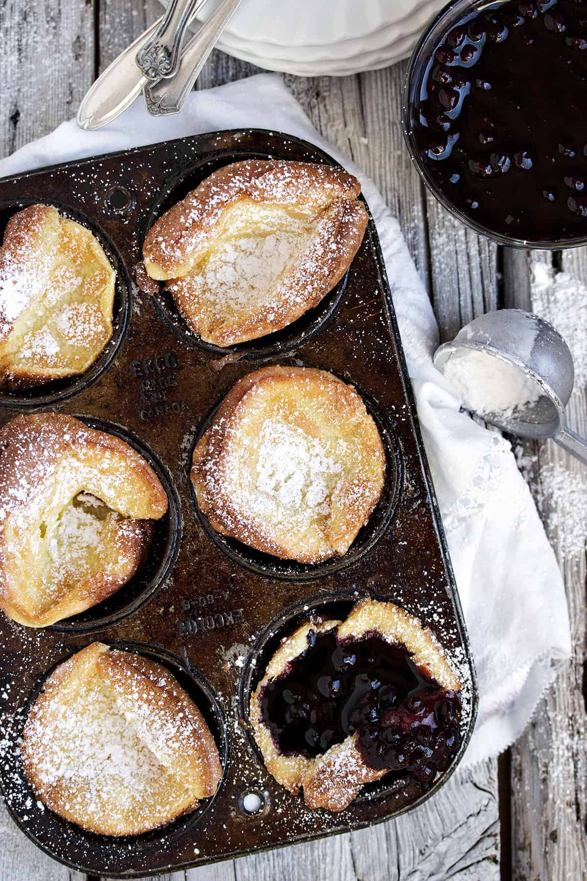 mini dutch babies in muffin tin with blueberry sauce