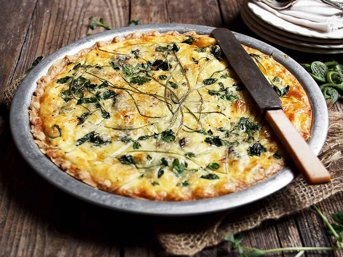 fiddlehead quiche in pie plate with knife