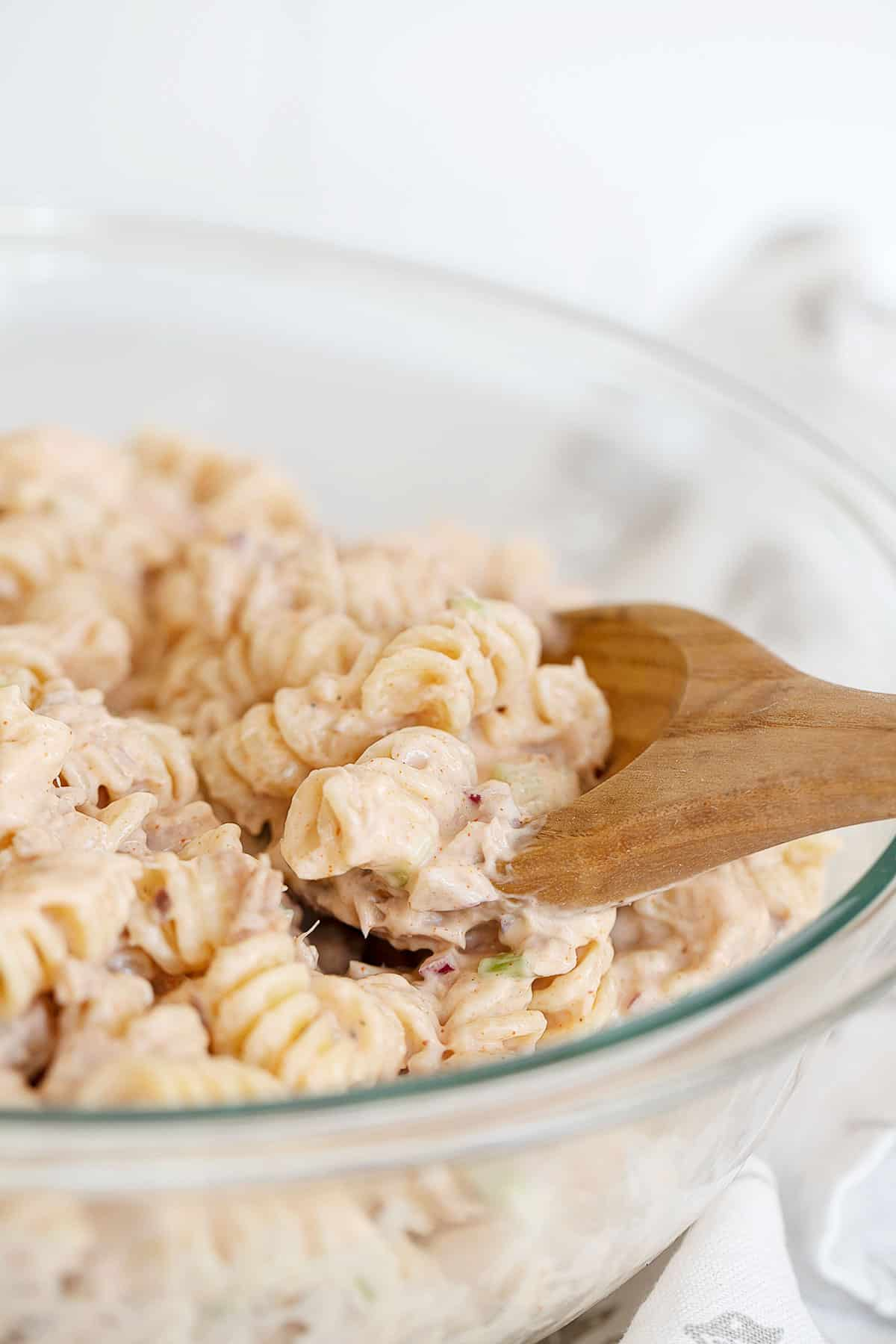 tuna pasta salad in glass bowl with wooden spoon