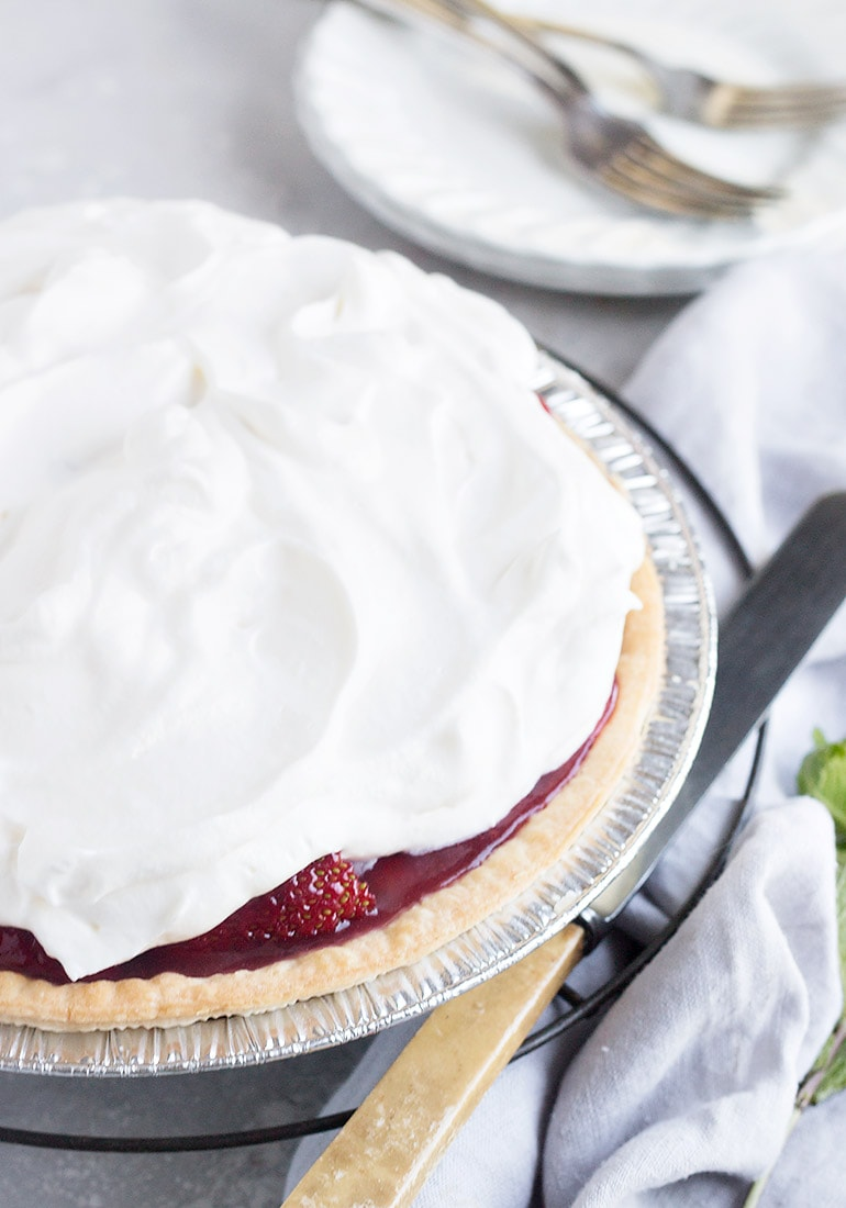 fresh strawberry pie topped with whipped cream