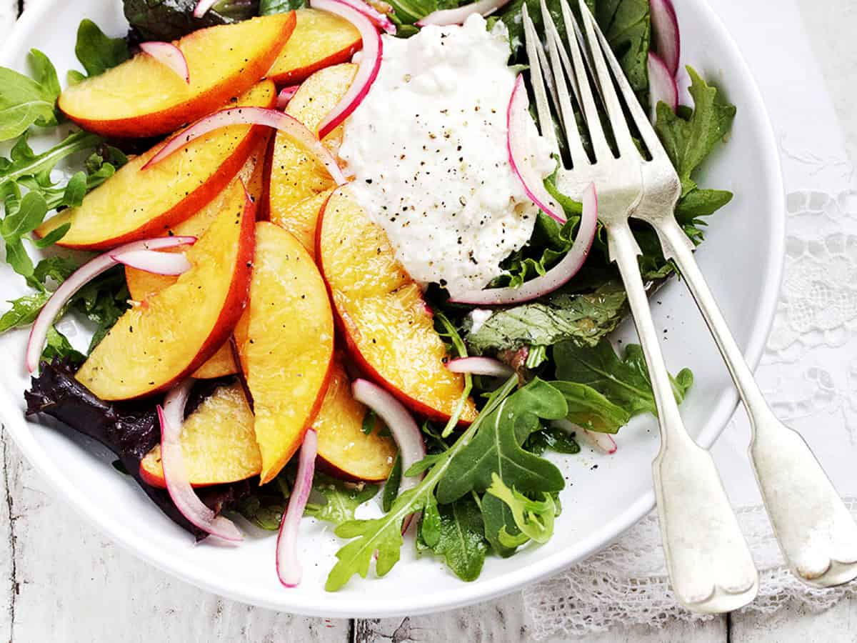 peach and burrata salad on white plate