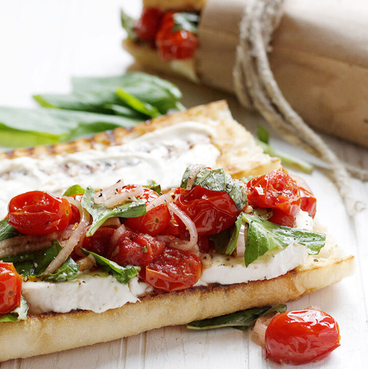 blistered tomato caprese sandwiches on white background