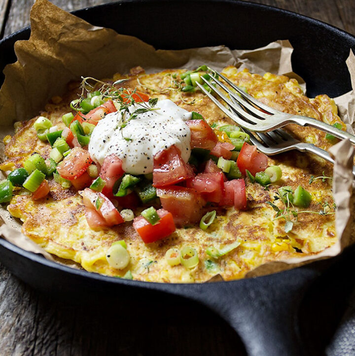 savoury corn pancake in skillet with jalapenos and tomatoes
