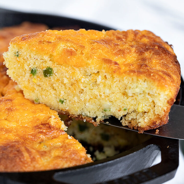 jalapeno cheddar cornbread in cast iron skillet with slice out