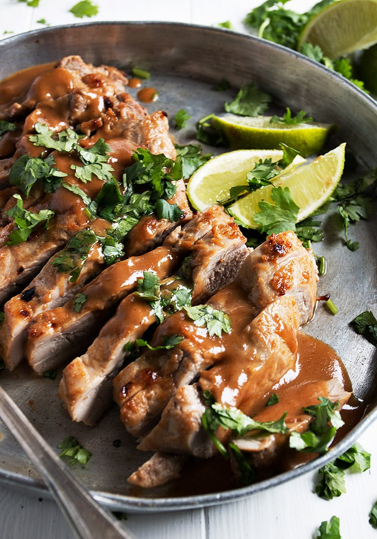 grilled pork tenderloin sliced with peanut sauce and lime wedges