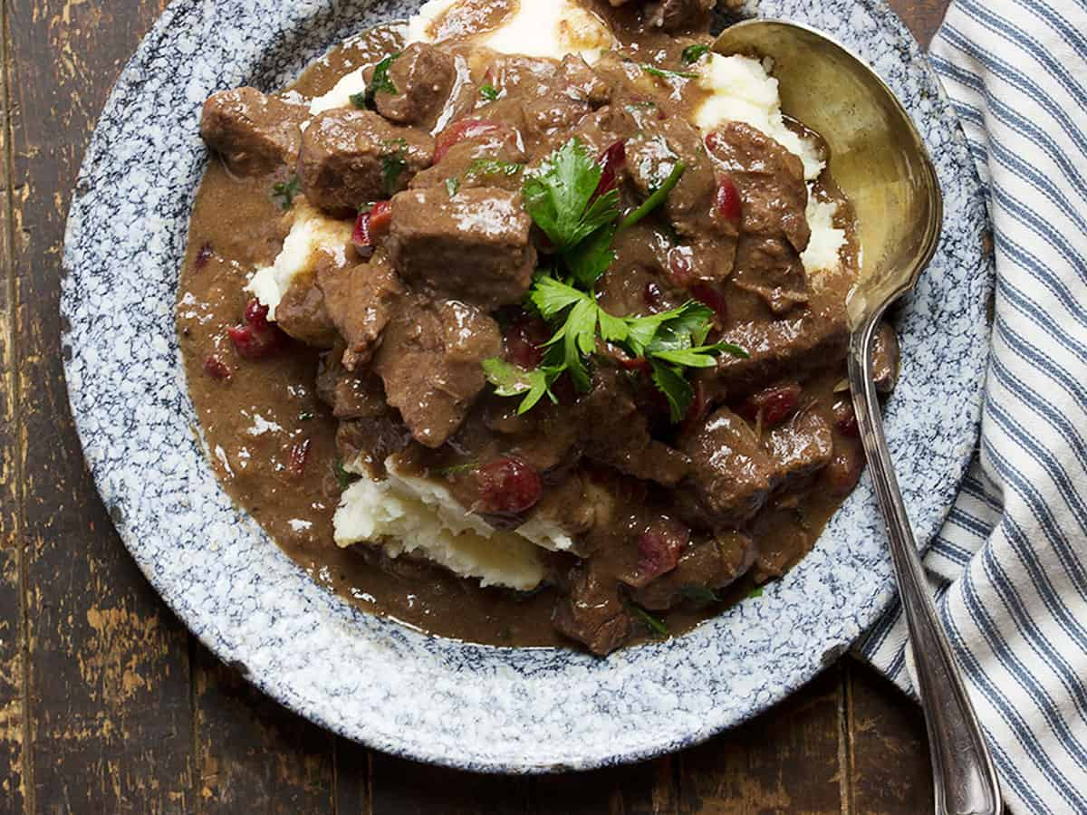 braised beef with cranberries on plate with mashed potatoes
