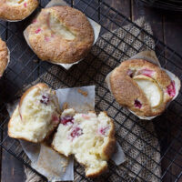 cranberry vanilla muffins split open on cooling rack