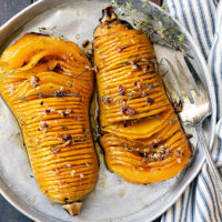 hasselback butternut squash on serving platter with fork