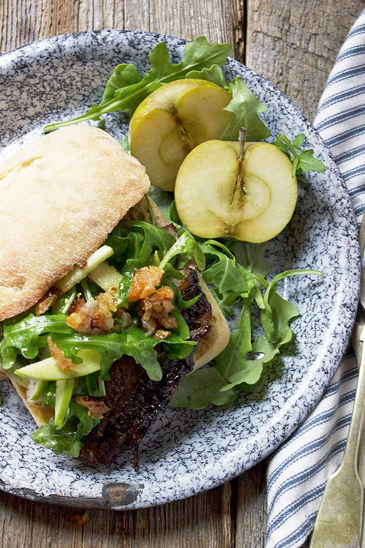 pork belly sandwich on plate with apple
