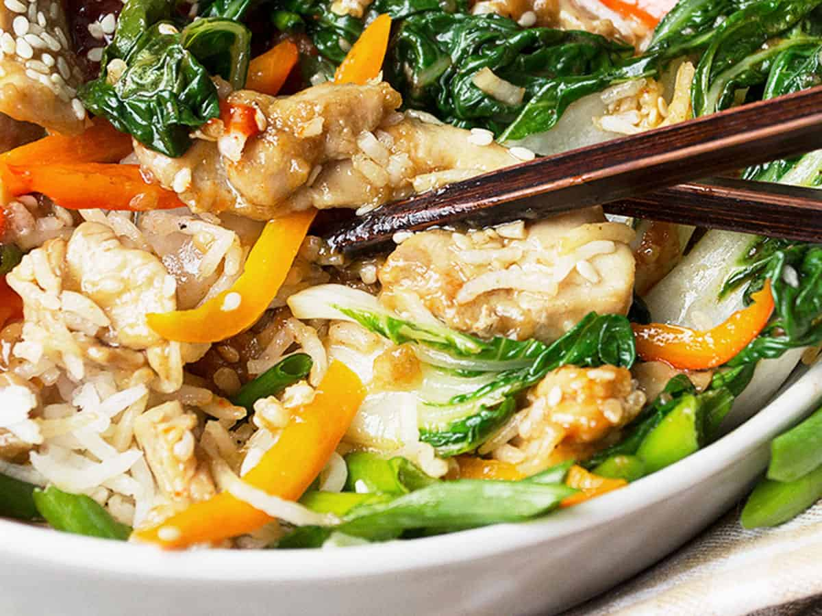 chicken bibimbap in bowl with sesame seeds and vegetables