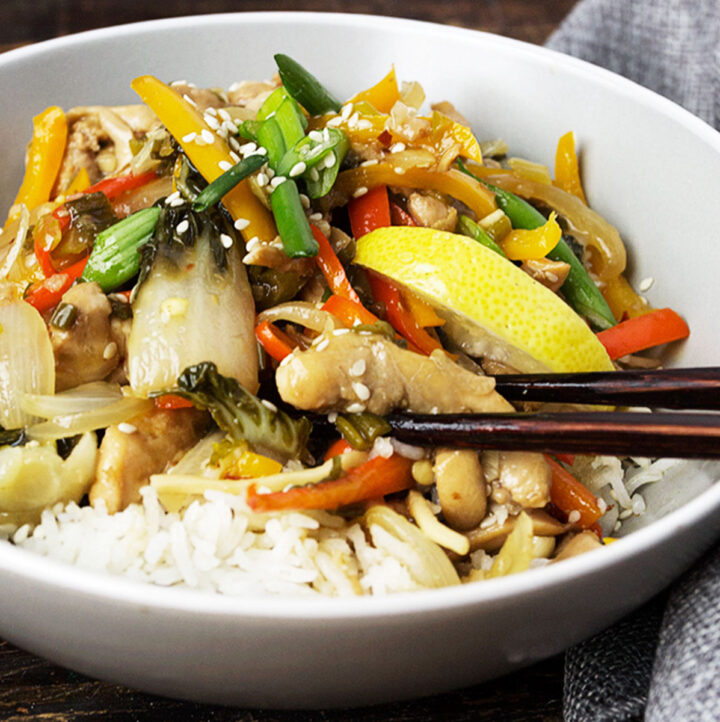lemon chicken stir fry in bowl with rice and chopsticks